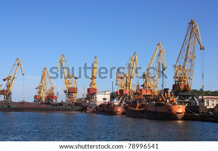 cranes in a port, unloading ships - stock photo