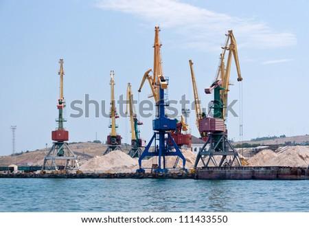 Cranes in cargo seaport on the Black Sea in Feodosia - stock photo