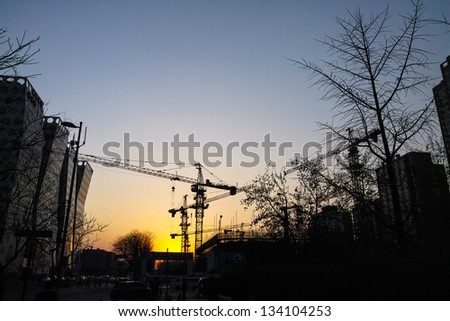 Cranes in the construction site under the sunset
