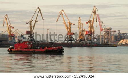 cranes in the sea port and tug - stock photo