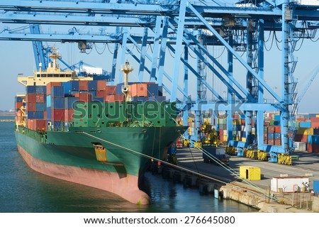 Cranes load containers on a large transport ship - stock photo