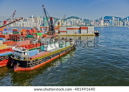 Cranes loading containers onto lighters in Hong Kong's Victoria Harbour.