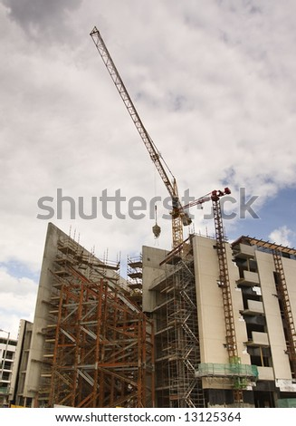 cranes looming over a large construction site - stock photo