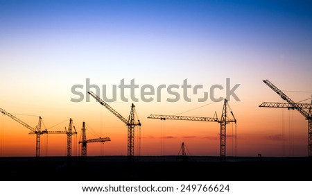 Cranes on a construction site against sunset sky - stock photo