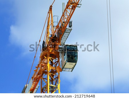 Cranes on the construction site on the background of cloudy sky  - stock photo