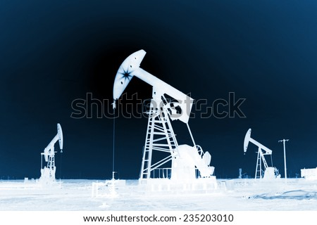 crank balanced beam pumping unit under the curtain of night in the JiDong oilfield, caofeidian, hebei province, China.   - stock photo