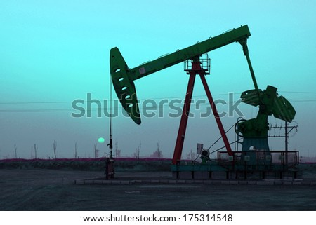 crank balanced beam pumping unit under the curtain of night in the oilfield, on December 1, 2013, caofeidian, hebei province, China.   - stock photo