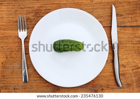 Crash dieting concept shot with whole cucumber on plate with fork and knife. - stock photo