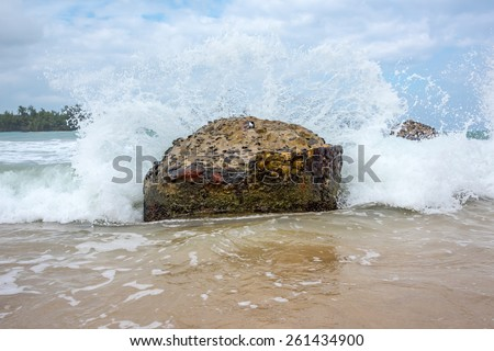Crashing wave upon old weathered pier pillar - stock photo