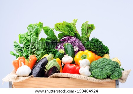 Crate of raw fresh vegetables from local farmers market isolated on light background, spinach kale beetroot aubergine broccoli peppers garlic aubergine capsicum garlic variety of healthy produce  - stock photo