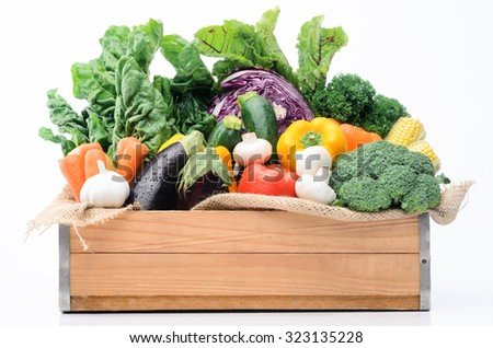Crate of raw fresh vegetables from the farmers market, assortment of corn, peppers, broccoli, mushrooms, beets, cabbage, parsley, tomatoes, isolated on light background - stock photo