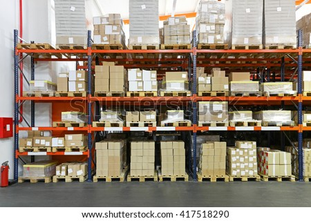 Crates and Boxes at Shelving System in Warehouse - stock photo