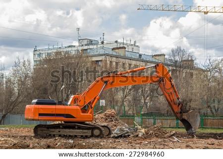 crawler excavator removes construction waste after building demolition - stock photo