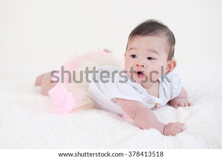 crawling baby playing on white blanket - stock photo