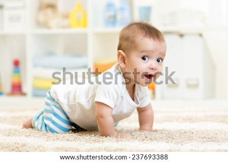 crawling funny baby boy indoors at home - stock photo