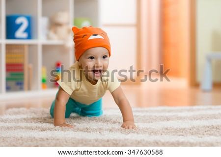 crawling kid or child at home on carpet - stock photo