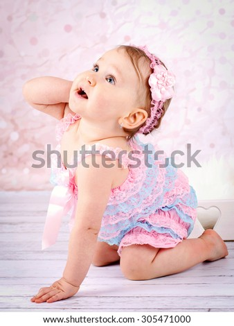 Crawling little baby girl with headband - stock photo