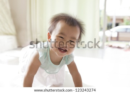 crawling of 10 month baby with funny face in home living room - stock photo