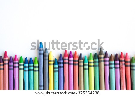 Crayons and pastels lined up isolated on white background with copy space - stock photo