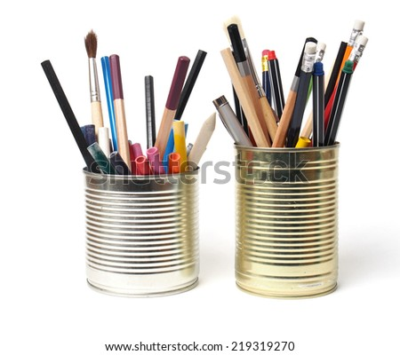 Crayons and pens in waste tin cans on white background - stock photo