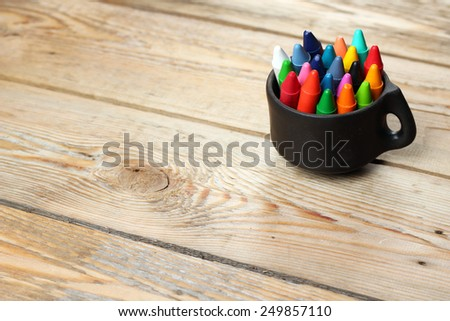 Crayons in a mug on a wooden table. Selective focus, copy space background - stock photo