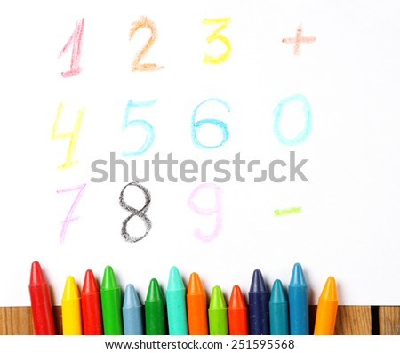 Crayons lying on a paper with children's drawing digit, number, sign. Selective focus, copy space background - stock photo