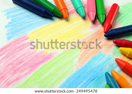 Crayons lying on an abstract hand drawing background. Selective focus, copy space background - stock photo