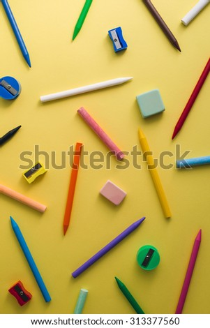 Crayons, pencil sharpeners, erasers and chalks of different colors on a yellow background - stock photo