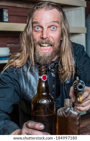 Crazed Western Man Aims Gun Towards You as he Sits at Table - stock photo - stock-photo-crazed-western-man-aims-gun-towards-you-as-he-sits-at-table-184997180