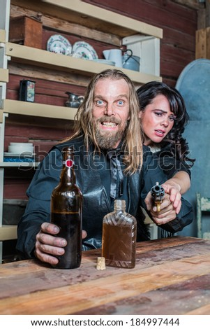 Crazed Western Man Aims Gun Towards You as he Sits at Table With Woman - stock photo