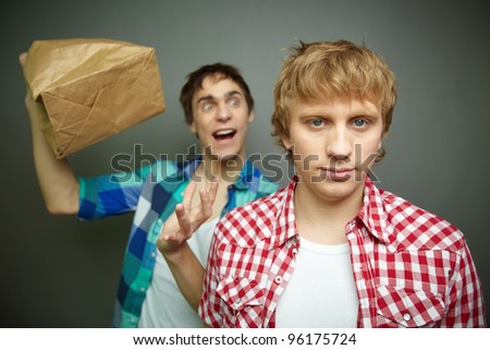 Crazily looking guy exploding paper bag behind his friend's back, fool's day series or birthday party - stock photo