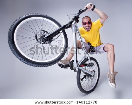 crazy boy on a dirt jump bike on grey background - wide studio shot ...