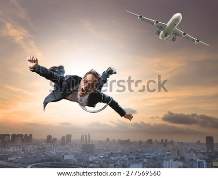 crazy business man flying from passenger plane with glad and happiness emotion use for new trend ,  people traveling ,and top secret strategy - stock photo