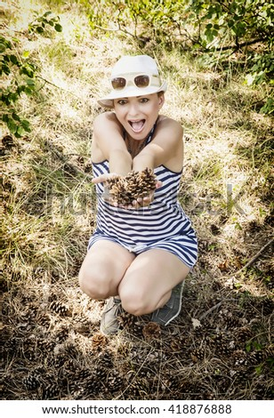 Crazy caucasian woman enjoying the pine cones in the forest by summer. Sailor outfit. Natural beauty. Beauty and fashion. Tourism theme. - stock photo