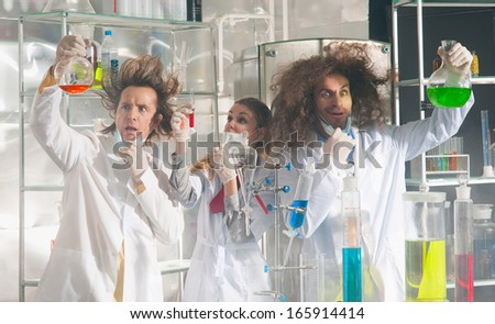 Crazy chemists conduct a scientific experiment in a laboratory - stock photo