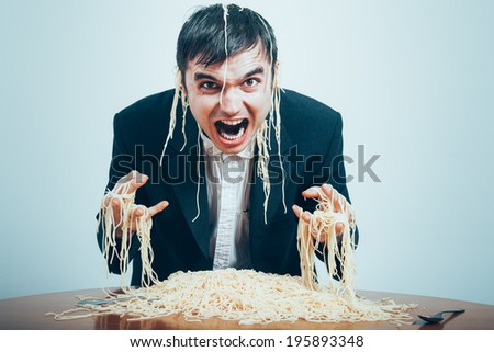 Crazy consumerism concept. Mad nasty businessman eating pasta on the table.