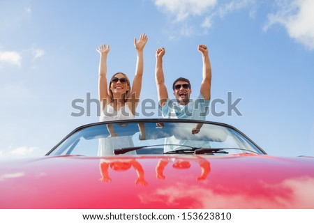 Crazy couple standing in red cabriolet on a sunny day - stock photo