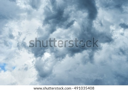 Crazy dark clouds are gathering displacing blue sky. Bright heaven background. Basic background for design