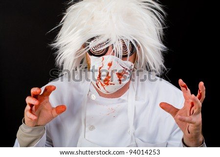 Crazy Doctor with a surgeon mask and scrubs splattered with blood.  Possibly a Halloween costume, maybe he's just nuts. - stock photo