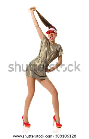 Crazy Fashion Girl. Shouting young woman in gold mini dress red high heels and sun visor cap pulls her long hair. Full length studio shot isolated on white. - stock photo