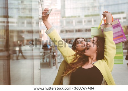 Crazy girls making shopping in the city center. Best friends spending time together and enjoying the afternoon In Milan city center - stock photo