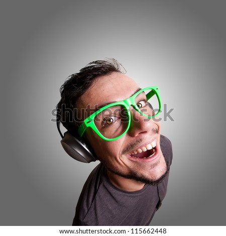 crazy guy listening to music with green eyeglasses - stock photo