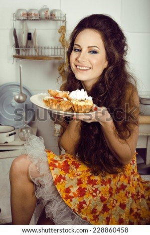 crazy housewife on kitchen smiling eating cakes - stock photo