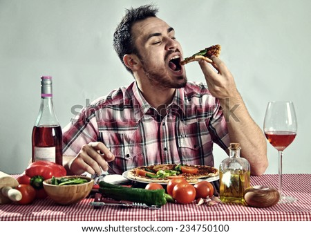 Crazy hungry man eating pizza in a restaurant - stock photo
