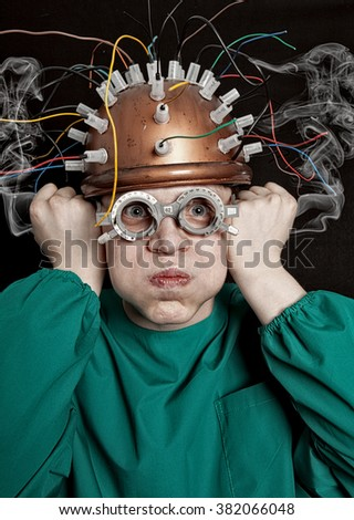 Crazy inventor with helmet for brain research - stock photo