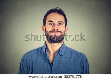 Crazy looking man making funny faces isolated on gray wall background   - stock photo