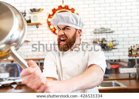 Crazy mad chef cook threatening with frying pan on the kitchen - stock photo