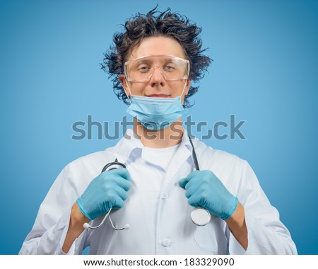 Crazy man doctor is holding stethoscope on a blue background - stock photo