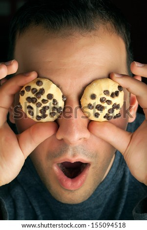 Crazy man holds cookies over his eyes. - stock photo