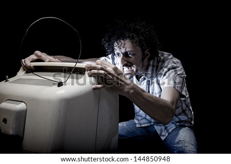 crazy man is shaking tv with his hands - stock photo